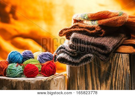 Stack of knitted winter socks on wood stand and yarn balls over fire background