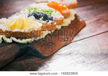 Toasts assortment. Bran bread, farmer cheese and various fresh tops. Served on wood