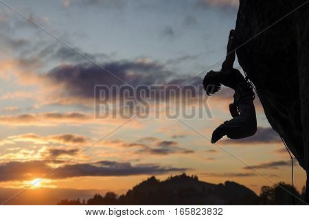 Silhouette Of Athletic Woman Climbing Steep Rock Wall