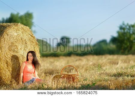 Girl sitting near a stack of straw