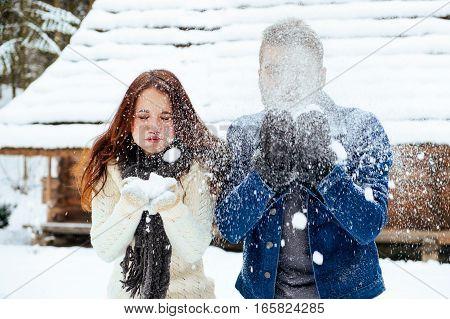 Winter couple having fun playing in snow outdoors. Young joyful happy multi-racial couple