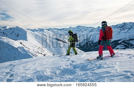 Two snowboarders on the mountain top just before riding down the