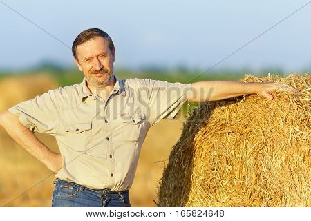 An elderly man is standing next to a stack of straw