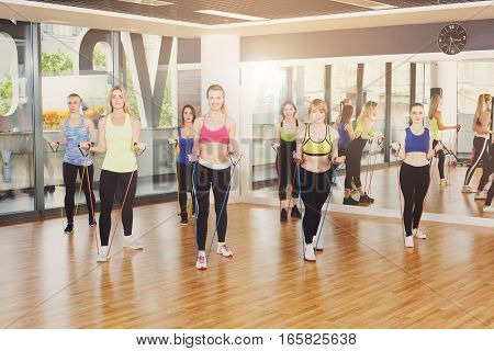Group of young women in fitness club making exercises with resistance band. Girls do training for hand muscles. Healthy lifestyle in sport club.