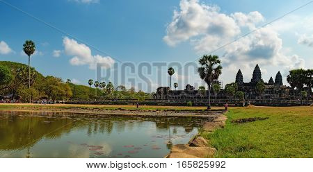 Siem Reap, Cambodia - February 1, 2016: Ruins and ancient pond with Lily, Angkor Wat temple, Cambodia. The main road to Angkor Wat which runs tours. Tourists visiting the sights and taking photos.