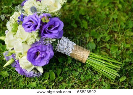 Close-up of wedding bouquet with white and purple flowers on green grass. Floristic conmosition