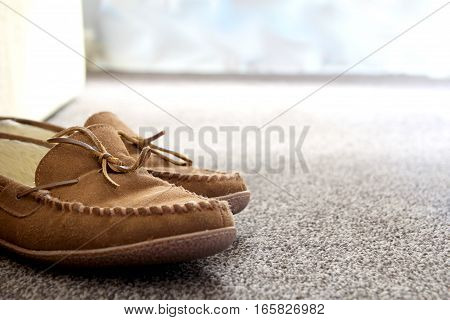 Generic Mens Suede Moccasin Slippers On Carpet Next To Sofa In A Nice Living Room. Copy Space For Te