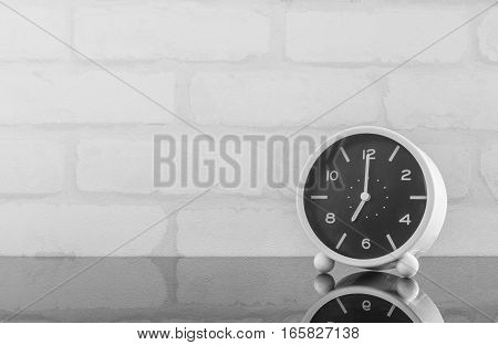 Closeup black and white alarm clock for decorate in 7 o'clock on black glass table and white brick wall textured background in black and white tone with copy space