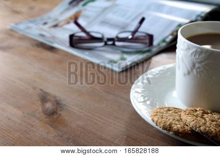 Tea And Biscuits Or Cookies, Magazine And Reading Glasses On A Wooden Coffee Table. Copy Space For T