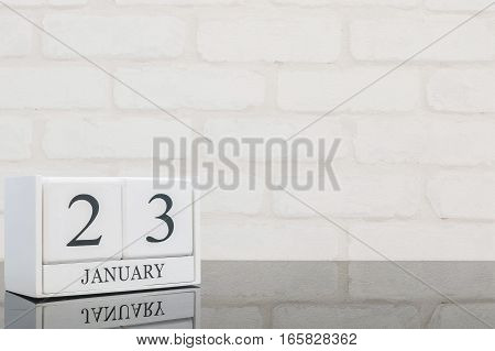 Closeup white wooden calendar with black 23 january word on black glass table and white brick wall textured background with copy space selective focus at the calendar