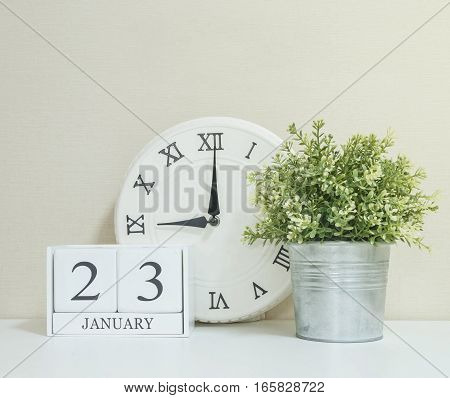 White wooden calendar with black 23 january word with clock and plant on white wood desk and cream wallpaper textured background selective focus at the calendar