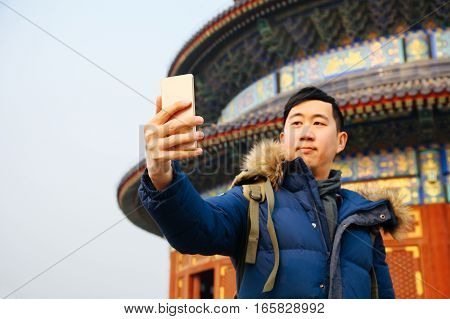 Asian Man Wearing Winter Jacket And Using A Smart Phone Over Chinese Temple Background (selective Fo