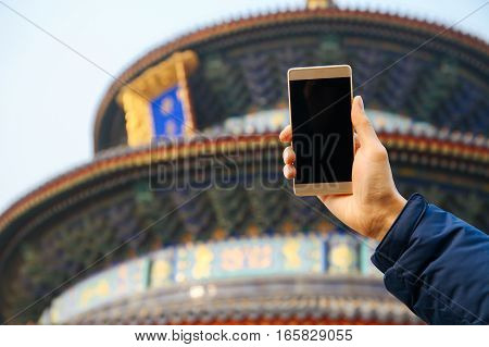 Closeup of man using a smart phone over Chinese temple background