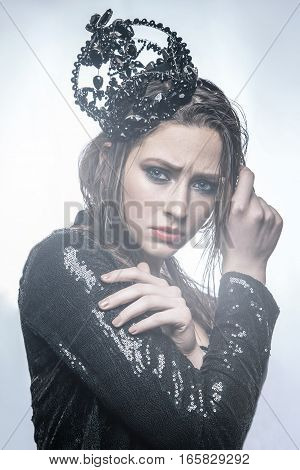 fashion beauty portrait of young beautiful young woman with makeup and freckles on her face with black crown on her head and black dress. with light from behind on light background.