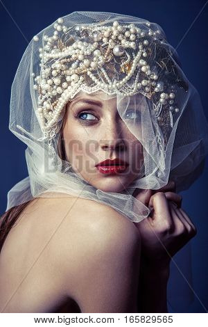 fashion beauty portrait of young beautiful young woman with makeup and freckles on her face and pearl headpiece on her head and white tulle in front of her face on dark blue background.