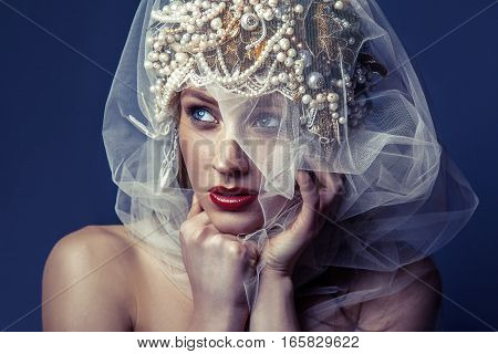 fashion beauty portrait of young beautiful young woman with makeup and freckles on her face and pearl headpiece on her head and white tulle in front of her face on dark blue background. poster