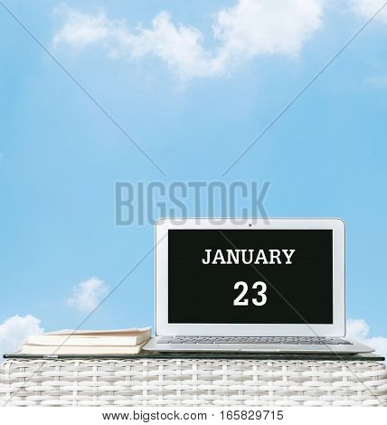 Closeup computer laptop with january 23 word on the center of screen in calendar concept on blurred wood weave table and book on blue sky with cloud textured background with copy space