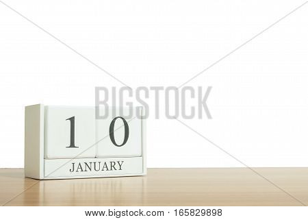 Closeup surface white wooden calendar with black 10 january word on blurred brown wood desk isolated on white background with copy space selective focus at the calendar