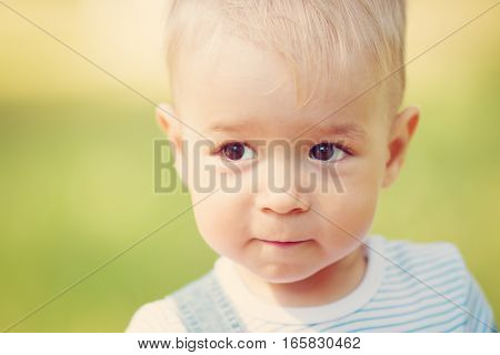 Happy little boy playing in the garden. Cute blond child portrait outdoors