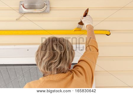 Woman with gloves colors the metal gas pipe of yellow paint with a brush with a wooden handle.