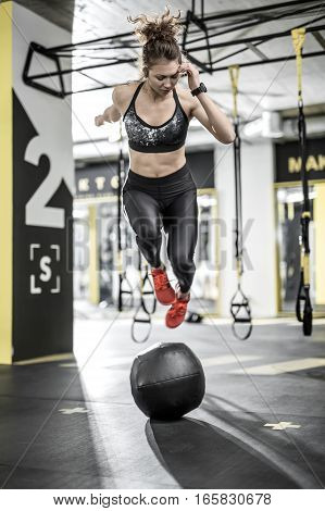 Sportive woman jumps above the black ball in the gym on the background of the hanging TRX straps. She wears dark top and pants, red sneakers. Vertical.