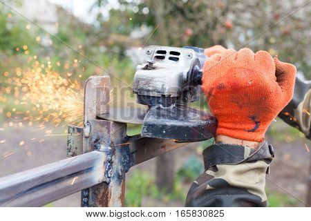 Closeup of a man using a grinder with cutoff blade to cut a section of pipe