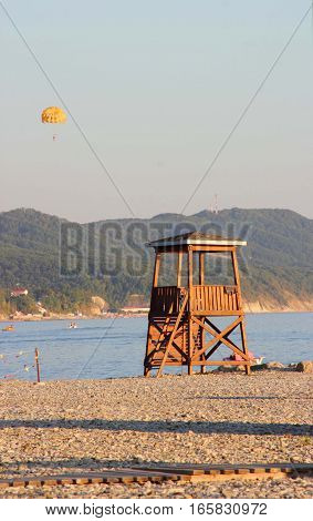 Lifeguard tower made of wood on a pebble beach on the background of mountains in sunset light