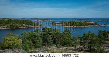An archipelago in Sweden taken from a small island mountain. Small islands with spruce trees and blue sea.
