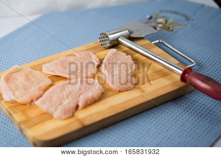 Chicken fillet on a wooden dostochka on a blue napkin. Crude chicken chops.