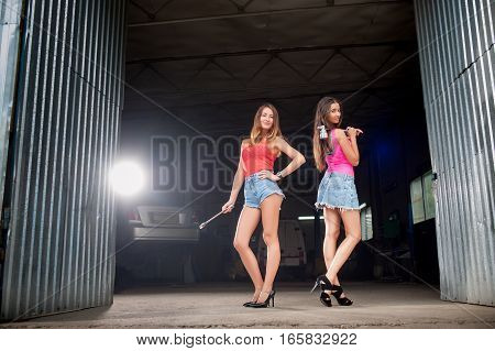Two Girls Standing At The Entrance To Car Repair Shop
