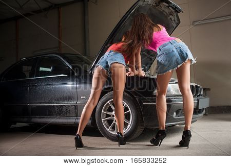 Two Sexy Girls Examining Car Engine At Auto Repair Shop
