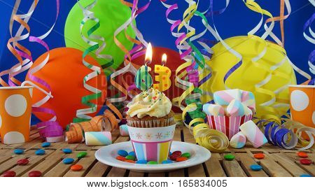 Birthday cupcake with candles burning on rustic wooden table with background of colorful balloons, plastic cups and candies with blue wall in the background