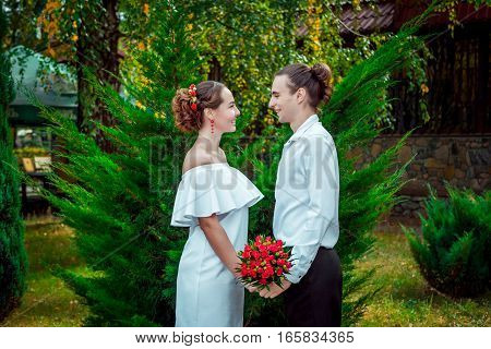 Happy loving wedding couple standing in the autumn park. Young handsome smiling  groom holding hands of at his beautiful bride in white dress with bouquet of red roses
