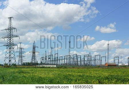 Transmission tower and electrical substation in the field and on the background of blue sky