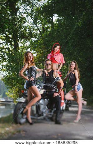 Portrait Of Biker And Three Sexy Girls
