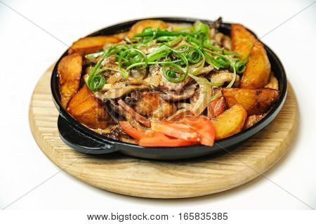 Fried potatoes with mushrooms onions and bacon. This dish is cooked in a pan. Served on a wooden board.