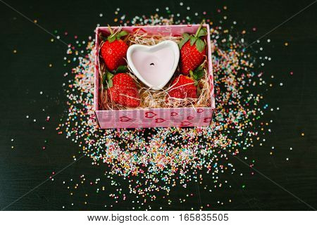 Strawberry and white candle in a box