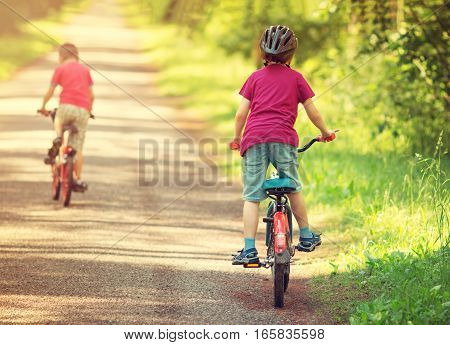 children riding on a bicycles at asphalt road in the park in summer
