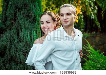 Happy loving wedding couple hugging in the autumn park. Beautiful young smiling  bride in white dress embracing groom