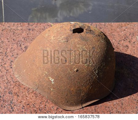 The old soldier's protective helmet. The helmet with a hole. The steel helmet on the monument.