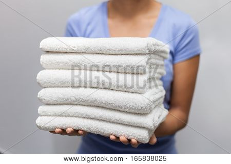 Maid holding a stack of white towels stock photo