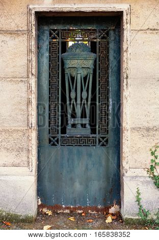Closed blue iron door of an abandoned tomb at a graveyard. The entry is rusty and weathered, decorated with geometric ornaments and a relief of a chalice or goblet with burning fire.