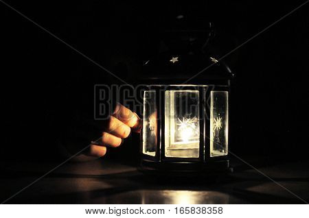 Hand fingers illuminated with light from candle lantern in dark black background with soft fire