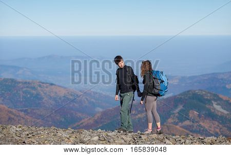 Young Happy Couple Hiking In The Beautiful Mountains