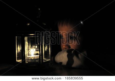 Boy looking at candle light in lantern candle light in black background with soft fire