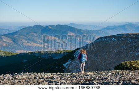 Young Girl Backpacker On The Ridge Of The Mountain