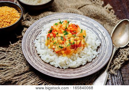 Yellow lentils Dahl with rice on wood background.