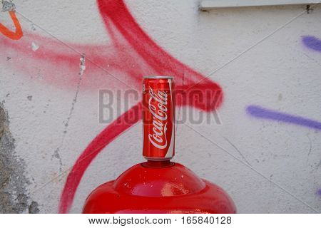 Venice Italy - September 9 2016: Coca Cola can standing on top of red hydrant at painted wall.