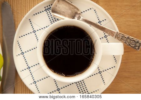 Cup of americano with spoon for break.