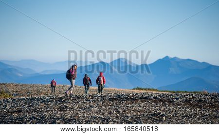 Group Of Four People Walking On The Rocky Mountain Plato